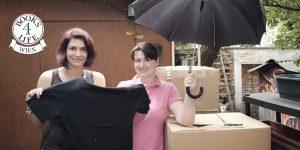 Die Geschäftsführerin von Books4Life Wien, Henriette Werner, übergibt Frau Zimmermann vom s'Häferl mehrere Kisten Sachspenden, darunter ein T-Shirt und einen Regenschirm.