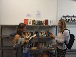 Zwei Frauen stöbern im offenen Bücherschrank